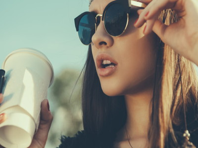 Pretty hipster girl in sunglasses with cup of coffee. Close-up lifestyle outdoor portrait